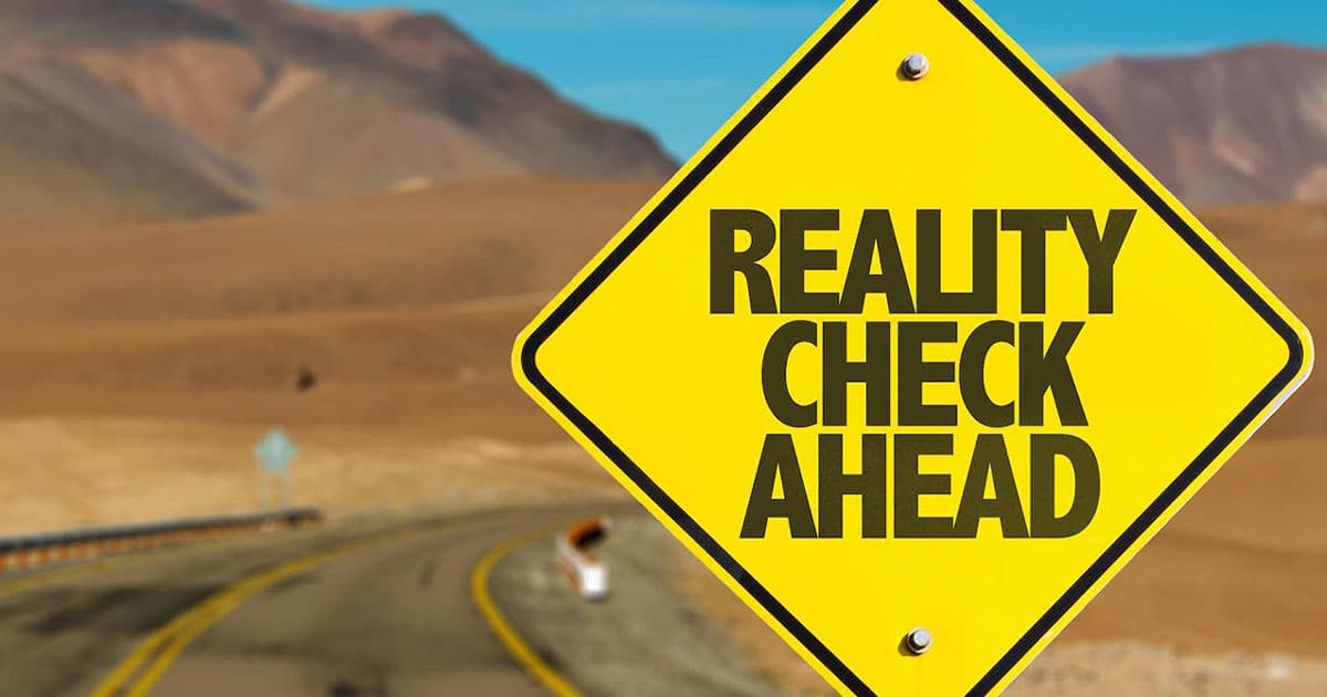 Road sign in a desert showing reality check ahead